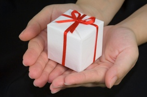 Hands holding a white gift box with red ribbon